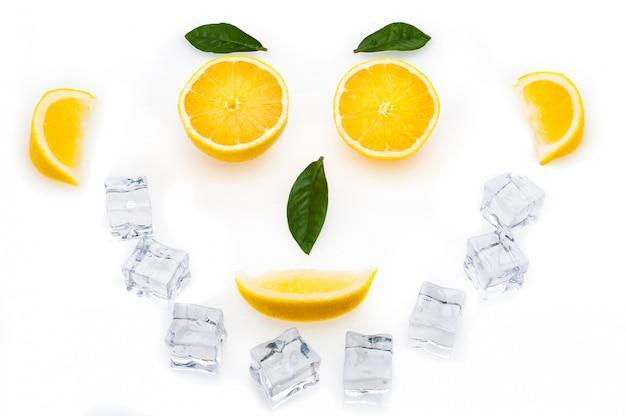 Heldere schijfjes citroen, groene bladeren en ijsblokjes in de vorm van een gezicht. het concept van een gezonde levensstijl.