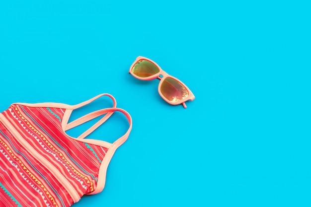 Heldere set voor een meisje voor een strandvakantie in trendy kleuren op een blauwe achtergrond.