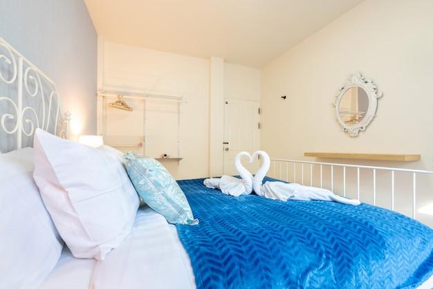 Heldere slaapkamer van het huis met zwaanhanddoek op het bed