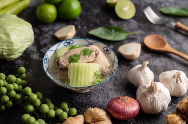 Heldere soep met kip met groen uitkomen met knoflook, citroen, ui, rode ui, champignons en basilicum