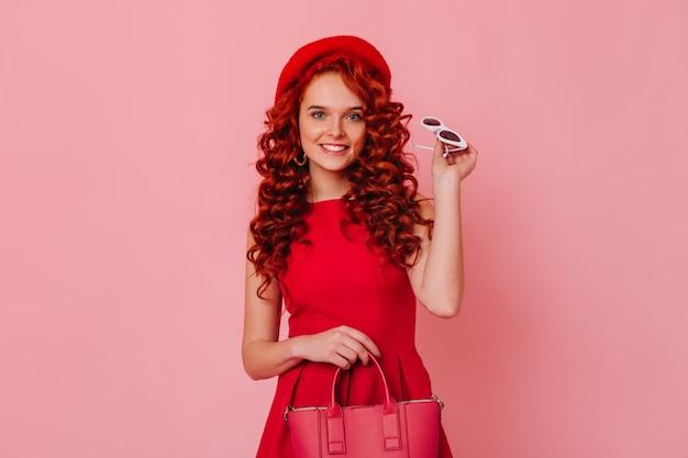 Heldere, spectaculaire blauwogige vrouw met rood haar in jurk en baret lacht en houdt een kleine stijlvolle tas op roze ruimte.