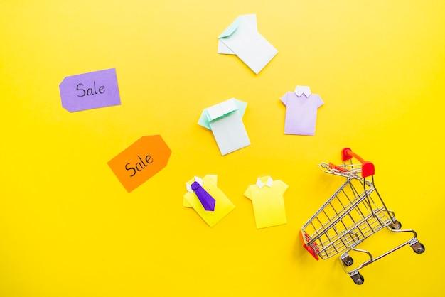 Heldere speelgoed papieren shirts in de buurt van het winkelwagentje en verkoop tags