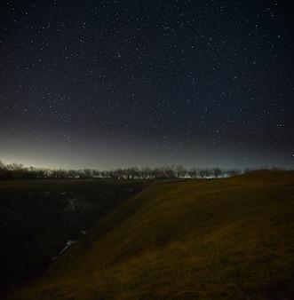 Heldere sterren aan de nachtelijke hemel, bossen en heuvels. landschap met een lange blootstelling.