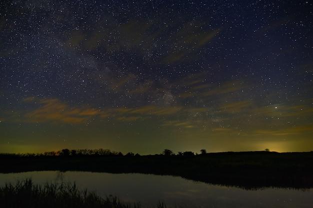 Heldere sterren met wolken boven de rivier in de nachtelijke hemel. outer space gefotografeerd met lange blootstelling.