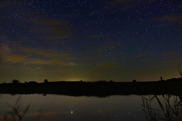 Heldere sterren met wolken boven de rivier in de nachtelijke hemel