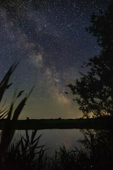 Heldere sterren van de melkweg boven de rivier in de nachtelijke hemel. outer space gefotografeerd met lange blootstelling.