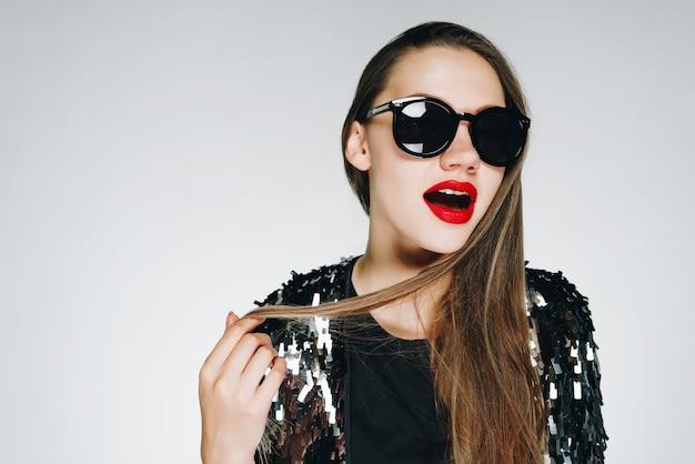 Heldere stijlvolle brunette met bril en een sprankelende zwarte blouse