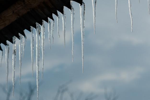 Heldere transparante ijspegels tegen blauwe hemel