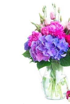 Heldere verse roze pioenroos, eustoma en blauwe hortensia bloemen boeket in vaas close-up geïsoleerd op wit
