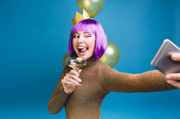 Heldere viering emoties van jonge vrouw met paarse kapsel selfie portret maken. gouden ballonnen, plezier hebben, tong, champagne, nieuwjaarsfeest, verjaardag tonen.