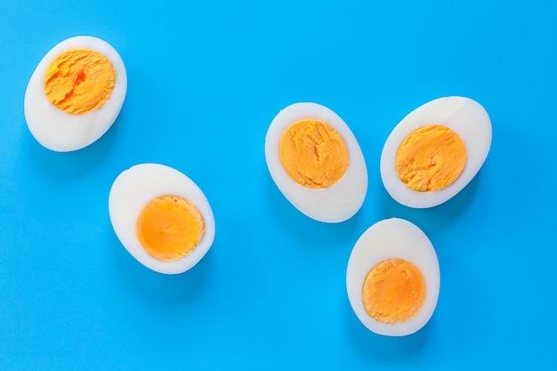 Heldere voedselachtergrond. helften gekookte eieren op een blauwe achtergrond