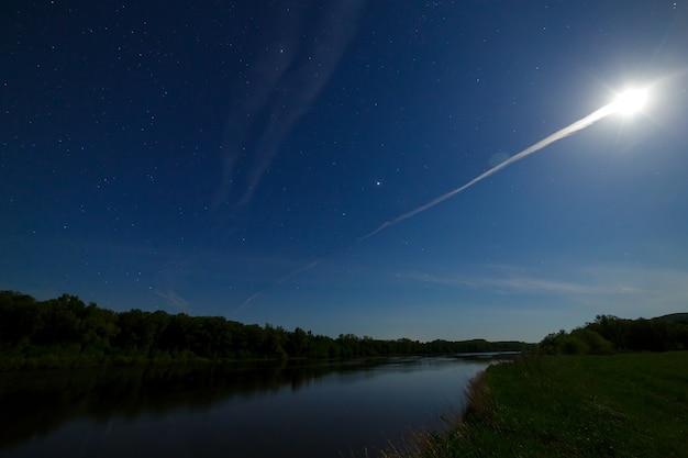 Heldere volle maan in de sterrenhemel boven de rivier
