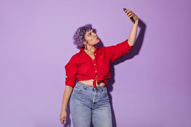 Heldere volwassen dame in stijlvolle ongebruikelijke kleding maakt foto op lila. kortharige krullende vrouw in rood shirt neemt selfie.