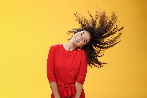 Heldere, vrolijke en zorgeloze speelse vrouw die met krullend haar zwaait en breed glimlacht als vrolijk in een rode jurk over een gele achtergrond in een goed humeur voor toekomstige avonturen. ruimte kopiëren