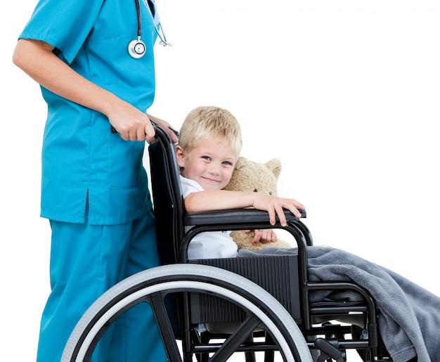 Heldere vrouwelijke arts die aanbiddelijke kleine jongen met zijn teddy draagt