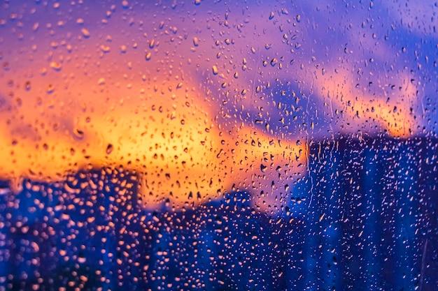 Heldere vurige zonsondergang door regendruppels op venster met bokehlichten. abstracte achtergrond. waterdruppel op het glas tegen de wazige silhouetten hoogbouw stad.