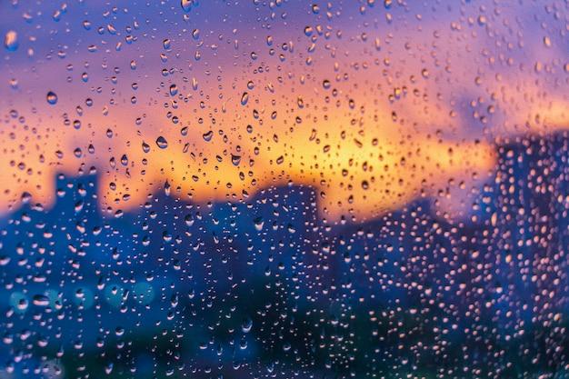 Heldere vurige zonsondergang door regendruppels op venster met bokehlichten. abstracte achtergrond