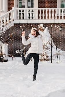 Heldere ware emoties van opgewonden stijlvolle vrouw met plezier in de sneeuw op straat in koude wintertijd. glimlachen, springen, gebreide muts, warme kleding, opgewekte stemming, wintervakantie, godsstemming.