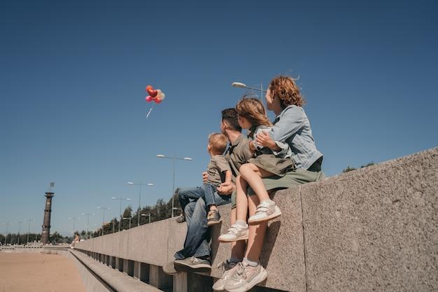 Heldere zomerfoto met een gelukkig gezin. ouders met kinderen kijken naar ballonnen. gezellige familiewandeling op het strand