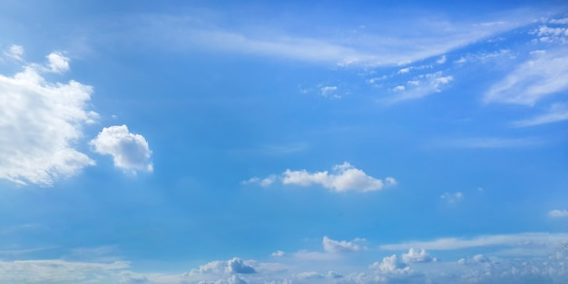 Heldere zonnige hemel met wolken op blauwe achtergrond