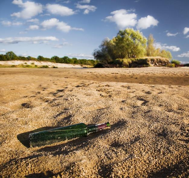 Heldere zonnige zomerdag, het zand aan de oever van de rivier, de oude groene fles wijn liggend op het zand, heldere blauwe lucht met wolken
