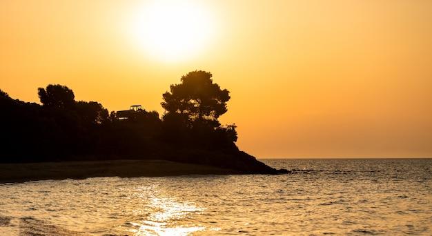 Heldere zonsondergang met grote gele zon het zeeoppervlak