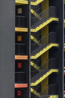 Heldergele externe brandtrap van nieuw parkeergebouw met meerdere niveaus in de stad