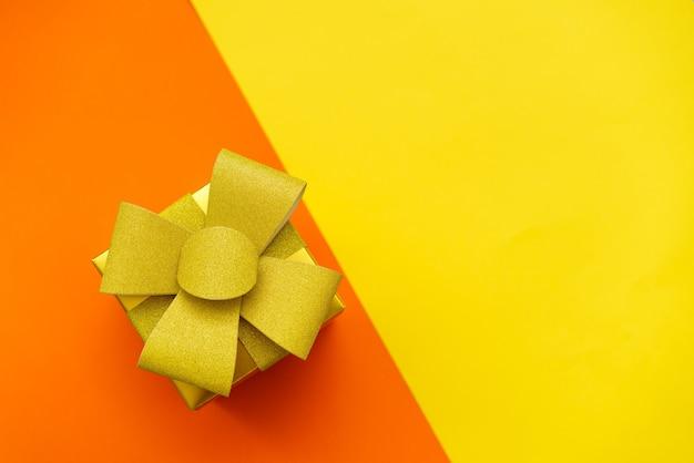 Heldergele geschenkdoos met gouden strik en lint op gele en oranje achtergrond plat lag feestelijke bac...