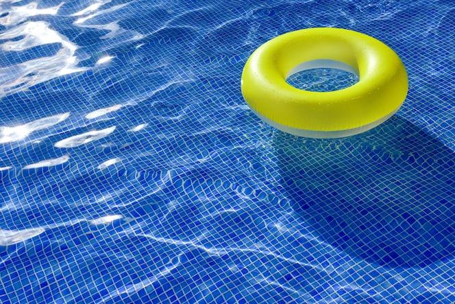 Heldergele opblaasbare reddingsboei in een buitenzwembad