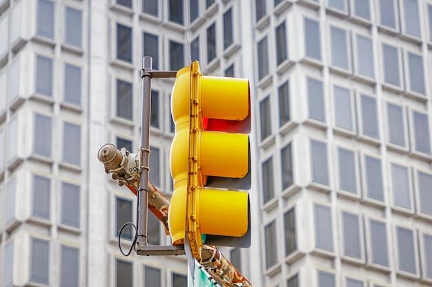 Heldergele verkeerslichten op het grijze vensterspatroon