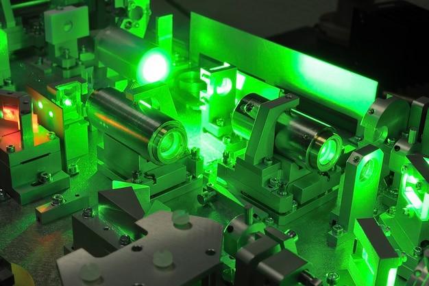 Heldergroen laserlicht dat naar binnen gaat, compliceert het wetenschappelijke systeem; selectieve focus op het centrale deel van de afbeelding