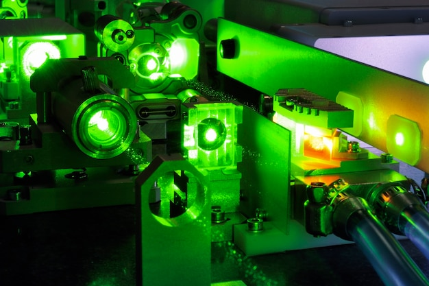 Heldergroen laserlicht dat naar binnen gaat, maakt het wetenschappelijke systeem met koelslangen binnenin gecompliceerd