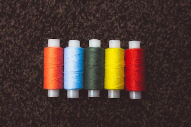 Helderrode, blauwe, groene, gele klosjes draad voor het naaien op een donkere achtergrond