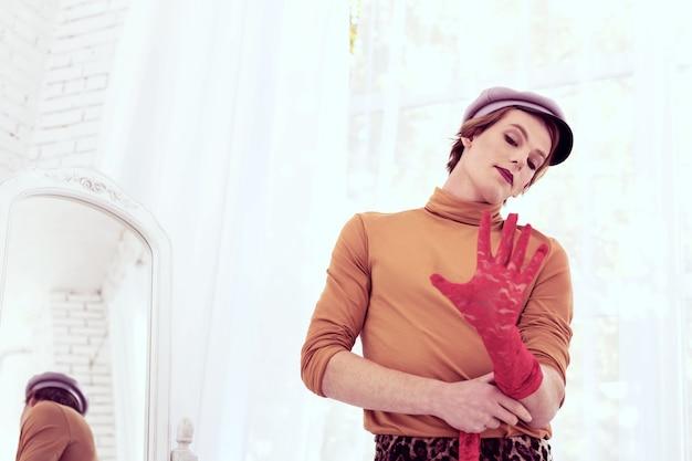 Helderrode handschoenen. knappe jonge transgender die opengewerkte lange mouwen probeert tijdens het kiezen van een avondje uit
