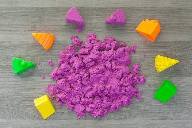 Helderroze kinetisch zand in de handen van een kind