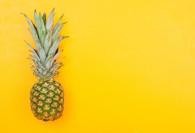 Hele ananas op een geel. bovenaanzicht.