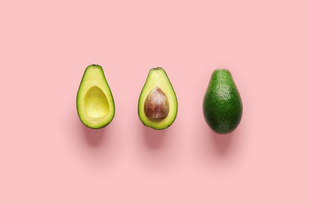Hele avocado fruit en twee helften op een rij geïsoleerd op roze achtergrond.