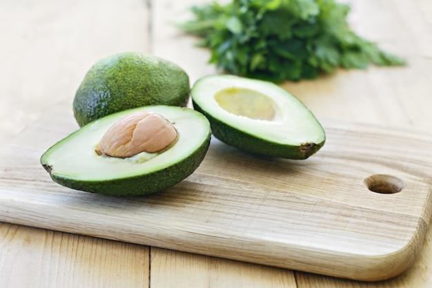 Hele avocado, peterselie of koriander op een houten bord