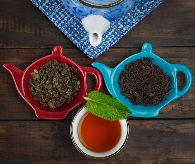 Hele blad thee met theepot en kopje met munt op houten tafel
