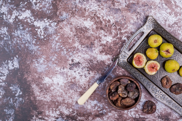 Hele, droge en gesneden vijgen in een metalen bakje en in een houten beker.
