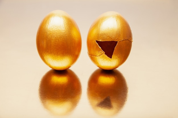 Hele en gebarsten gouden eieren geplaatst op reflecterende tafel