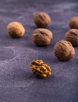 Hele en gebarsten walnoten op blauw gestructureerd oppervlak, zijaanzicht. gezonde samenstelling van noten en zaden.