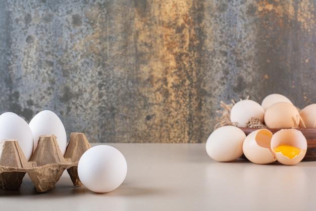 Hele en gebroken verse rauwe eieren op beige tafel.