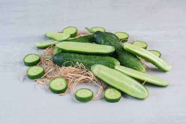 Hele en gehakte komkommers op stenen oppervlak. hoge kwaliteit foto