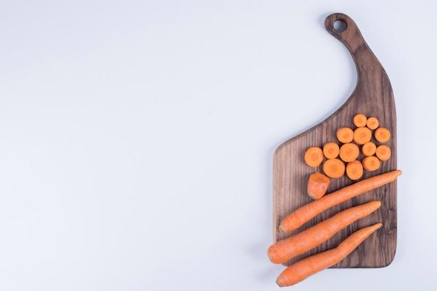 Hele en gehakte wortelen op een houten bord.