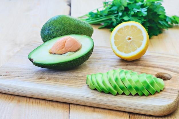 Hele en gesneden avocado en citroen, peterselie of koriander op een houten bord