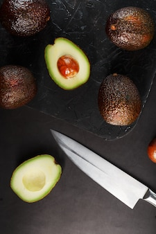 Hele en gesneden avocado's met een mes op een zwarte getextureerde zwarte tafel