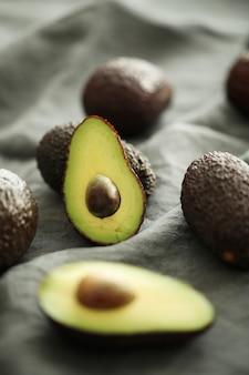 Hele en gesneden avocado's op grijze doek