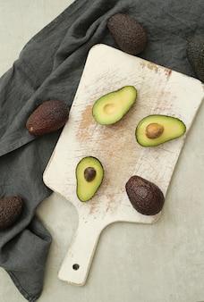 Hele en gesneden avocado's op houten snijplank