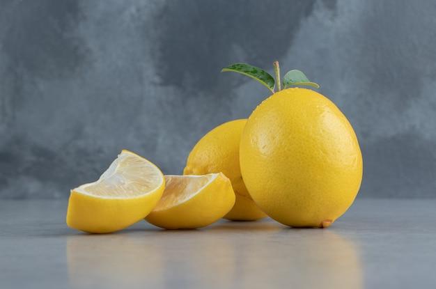 Hele en gesneden citroenen op marmer